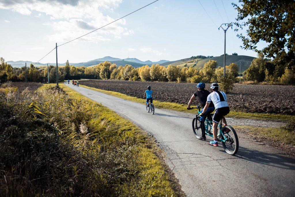 Dos ciclistas en tándem detrás de otro ciclista recorren un camino asfaltado rodeado de árboles otoñales.