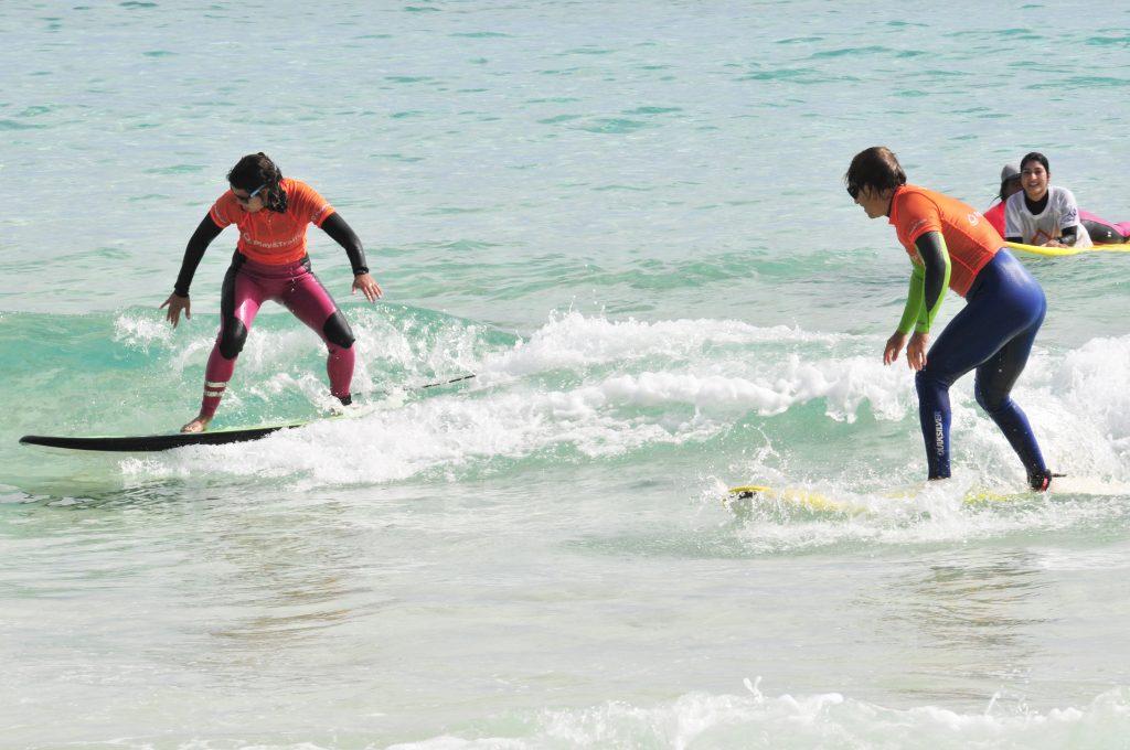 Bego Curero y Jon Santacana de pie en una ola.