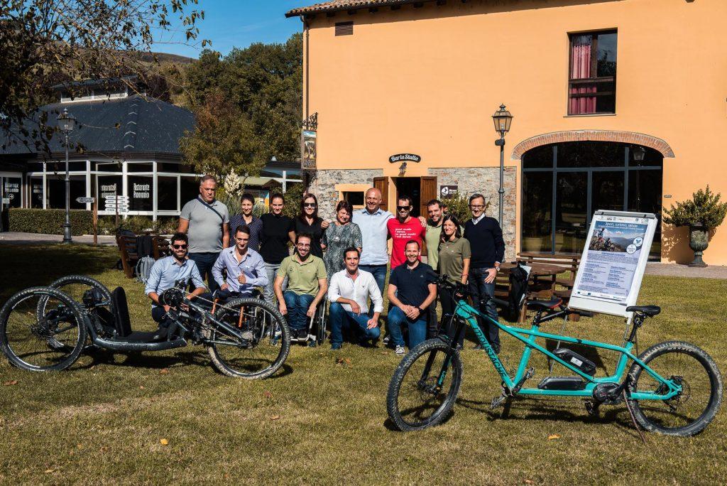 Un grupo de personas sonríe al lado de las bicicletas adaptadas, una handbike y un tándem, y junto al cartel de la jornada.