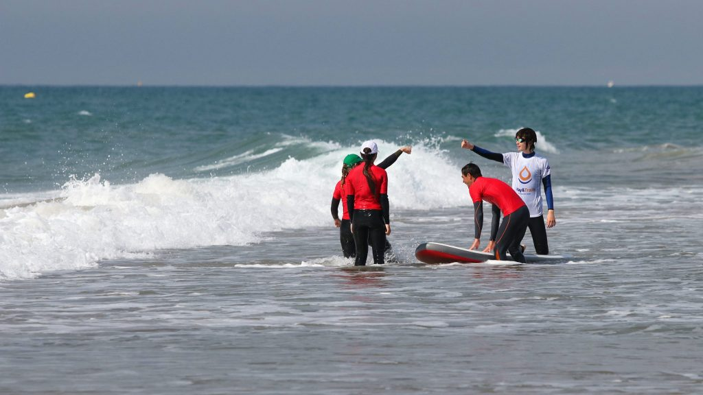 Dentro del mar un monitor aguanta la tabla de surf mientras otro choca el puño con un chico