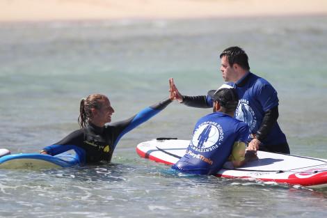 Chico dentro del agua con la tabla de surf chocando la mano a los instructores